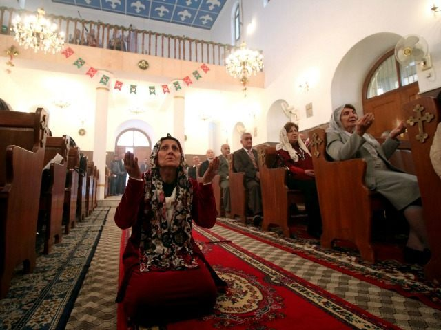 An Iraqi Christian woman prays at the Chaldean church in the southern city of Basra on January 1, 2016.