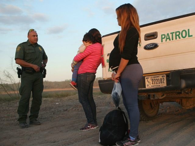 An immigrant from El Salvador, seven months pregnant, she said, stands next to a U.S. Border Patrol truck after she and others turned themselves in to border agents on December 7, 2015 near Rio Grande City, Texas.