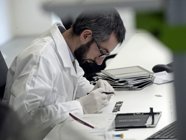 A technician repairs a tablet on November 7, 2014 at the 'Allo Smartphone' company in Paris. The company collects and repairs all kind of smartphones before bringing them to the market.