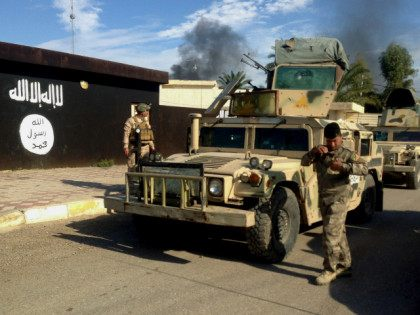 FILE - In this Monday, Nov. 24, 2014 file photo, Iraqi army soldiers deploy in front of a court run by the Islamic State group after a military operation to regain control of the town of Sadiyah in Diyala province, 60 miles (95 kilometers) north of Baghdad, Iraq. Questions persist …