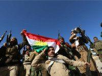 IRAQ, SINJAR : Iraqi autonomous Kurdish region's peshmerga forces and fighters from the Yazidi minority, a local Kurdish-speaking community which the Islamic State (IS) group had brutally targeted in the area, raise the Kurdish flag in northern Iraqi town of Sinjar, in the Nineveh Province, on November 13, 2015. Iraqi …