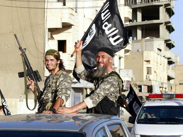 Militant Islamic State fighters wave flags as they take part in a military parade along the streets of Syria's northern Raqqa province June 30, 2014. REUTERS/Stringer