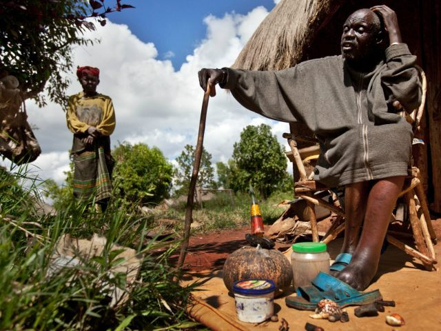 Kenyan witch-doctor John Dimo, who claims to be 105 years old, interprets the result after throwing shells, bones, and other magic items to predict the outcome of the U.S. election, in front of his hut in the village of Kogelo, from where President Barack Obama's late father came from and whom Dimo claims he knew, in western Kenya Monday, Nov. 5, 2012. While pollsters in the U.S. are using armies of live-interviewers, statistical analysis and the latest automated polling technology, Dimo, who inherited the work from his father in 1962 and has two wives and five children, is confident of his traditional methods and claimed the result would go in Obama's favor. (AP Photo/Ben Curtis)