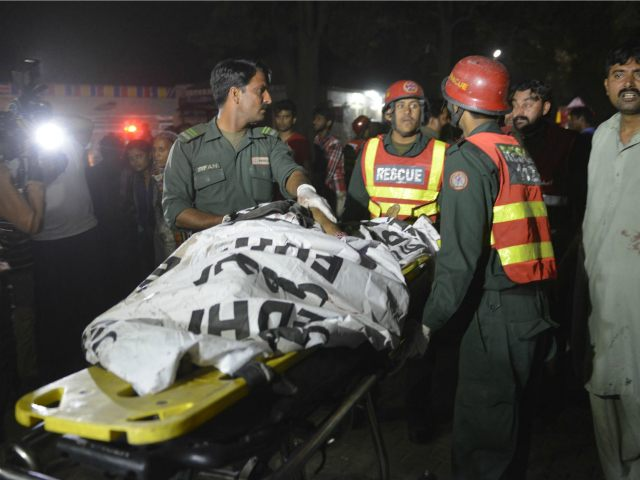 PAKISTAN, Lahore : Pakistani rescuers use a stretcher to shift a body from a bomb blast site in Lahore on March 27, 2016. At least 25 people were killed and dozens injured when an explosion ripped through the parking lot of a crowded park where many minority Christians had gone to celebrate Easter Sunday in the Pakistani city Lahore, officials said. / AFP / ARIF ALI