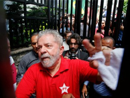 Brazil's former President Luiz Inacio Lula da Silva greets supporters who have gathered outside his residence, in Sao Bernardo do Campo, in the greater Sao Paulo area, Brazil, Saturday, March 5, 2016. Brazilian police hauled in the former president for questioning Friday, in a sprawling corruption case centered on the …