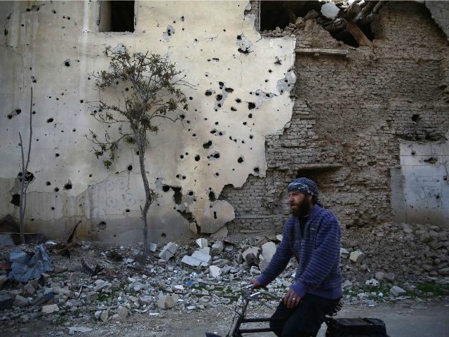 Syria, Jobar : CORRECTION / A Syrian man rides a bike in the neighbourhood of Jobar, on the eastern outskirts of the capital Damascus, on January 23, 2016.