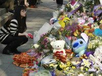 A woman visits a makeshift memorial for a girl who was attacked to death Monday by a knife-wielding assailant outside a subway station in Taipei, Taiwan, Tuesday, March 29, 2016. A transit police officer was stabbed in the head at another subway station in the city Tuesday, a day after a 3-year-old girl was decapitated in apparently random knife attacks in Taiwan's capital. (AP Photo/Chiang Ying-ying)