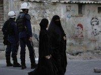 Bahraini women pass by riot police watching for protesters, to prevent a third day gathering of demonstrators against Saudi Arabia's execution of Shiite cleric Sheikh Nimr al-Nimr in Daih, Bahrain, a largely Shiite suburb of the capital, Monday, Jan. 4, 2016. Graffiti on the wall is of people killed in …