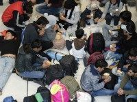 Refugees eat as they sit on the ground at the hall of the main train station in Salzburg, near the German-Austrian border, on September 16, 2015 as tens of thousands of migrants have entered Austria from Hungary in recent weeks.