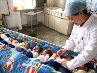 ZHANGJIAKOU, CHINA - OCTOBER 01: (CHINA OUT) A nursing worker takes care of new-born babies at the Second Affiliated Hospital of Hebei North University on October 1, 2015 in Zhangjiakou, Hebei Province of China. China has decided to abandon its 35-year-old one-child policy, allowing all couples to have two children, …