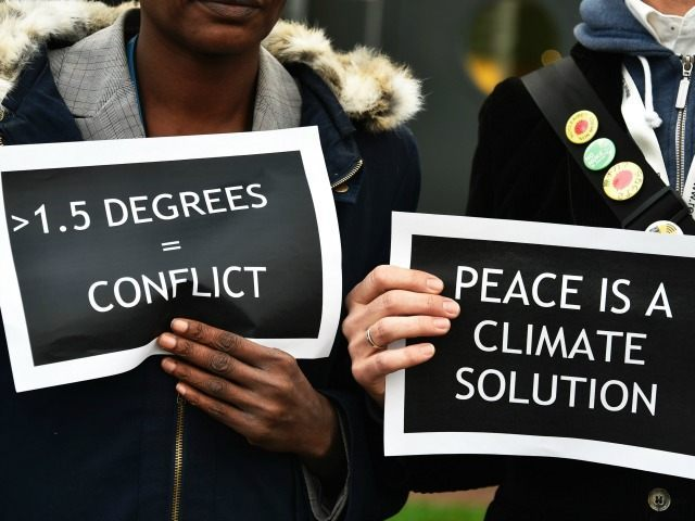 People hold placards as they demonstrate during the United Nations conference on climate change (COP21) in Le Bourget on December 11, 2015