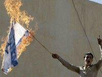 A Jordanian protester holds a burning Israeli flag during a demonstration near the Israeli Embassy in the capital Amman in solidarity with the Palestinians on October 16, 2015.