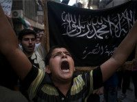 FILE - In this Sept. 21, 2012 file photo, a Syrian boy shouts slogans against the government as he stands in front of a flag of the armed Islamic opposition group, the Nusra Front, during a demonstration in the Bustan al-Qasr neighborhood of Aleppo, Syria. The country has already been …