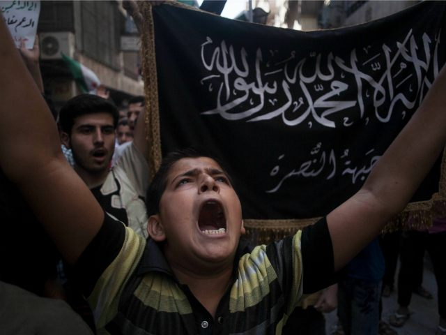 FILE - In this Sept. 21, 2012 file photo, a Syrian boy shouts slogans against the government as he stands in front of a flag of the armed Islamic opposition group, the Nusra Front, during a demonstration in the Bustan al-Qasr neighborhood of Aleppo, Syria. The country has already been shattered by more than four years of civil war, and with no solution in sight some players on the ground and observers outside have concluded its fate will be to break up along sectarian or regional lines, in a best-case scenario, tenuously held together by a less centralized state. (AP Photo/Manu Brabo, File)