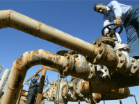 File picture dated 19 January 2004 shows Iraqi workers turning valves at the Shirawa oilfield, where oil was first pumped in Iraq in 1927, outside the northern Iraqi city of Kirkuk.