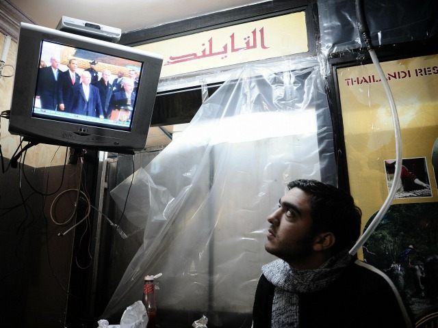 A Palestinian man watches the live televised inauguration ceremony for US President Barack Obama at a restaurant in Gaza City on January 20, 2009.