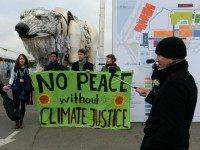 Activists hold a banner reading 'No peace without climate justice' in front of a giant polar beer puppet called Aurora by environmental organization Greenpeace during a demonstration at the venue of the COP21 United Nations climate change conference in Le Bourget, on the outskirts of Paris, on December 11, 2015.