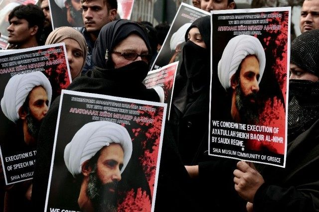 TOPSHOT - Members of the Shia Muslim community of Greece hold up placards and banners bearing images of prominent Shiite cleric and activist Nimr al-Nimr during a demonstration near the Saudi Arabian embassy in Athens on January 6, 2016, as they condemn Nimr's execution by Saudi authorities. Nimr, one of …