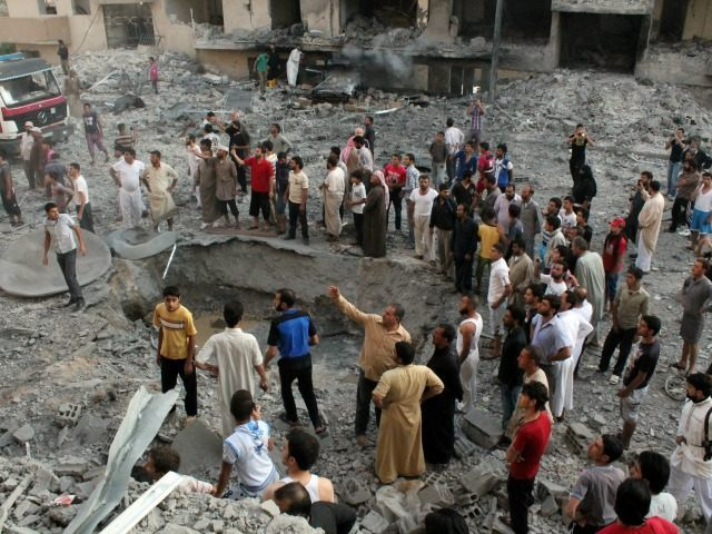 People gather around a crater at the scene of an explosion in the northern Syrian city of Raqqa, early on August 7, 2013. UN weapons inspectors tasked with looking into claims of chemical weapons use in Syria are 'completing their preparations' in The Hague before heading to Damascus, the United …