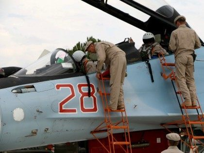 Russian servicemen assist air force pilots in a Russian Sukhoi Su-30SM fighter jet before departure on a mission at the Russian Hmeimim military base in Latakia province, in the northwest of Syria, on December 16, 2015.