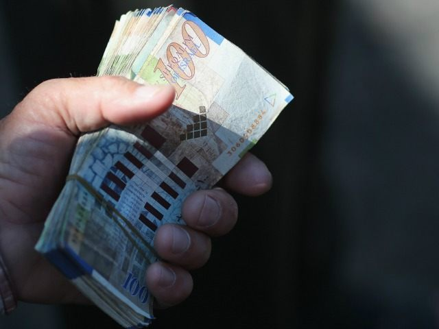 A money exchanger holds a handful of Israeli shekels in the market place on June 12, 2015, Gaza City, Gaza.