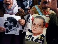 Supporters of Egypt's former president Hosni Mubark (portraits) shout slogans praising the ousted leader outside the appeals court in Cairo on November 05, 2015, as the court opened the retrial of the veteran strongman on charges of orchestrating the murders of protesters during the 2011 Arab Spring uprising that toppled …