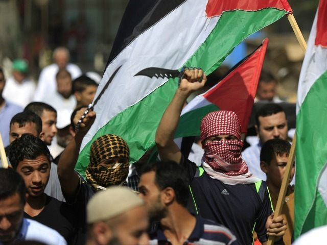 Palestinian protesters carry knives and the national flag during a demonstration in the Jabalia refugee camp, in northern Gaza on October 16, 2015.