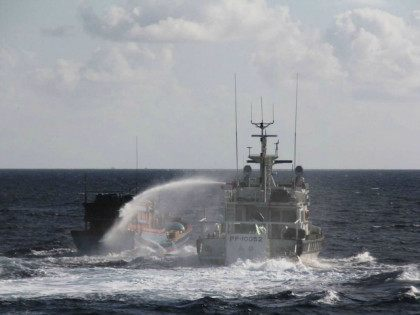 AT SEA : This handout photo taken on January 6, 2016 and released on January 25, 2016 by the Taiwan Coast Guard shows Taiwan's coastguard (R) using a water cannon to spray a Vietnamese fishing boat, some 2.5 nautical miles (around 4,600 metres) off Taiping Island, an Taiwan-administered islet in …