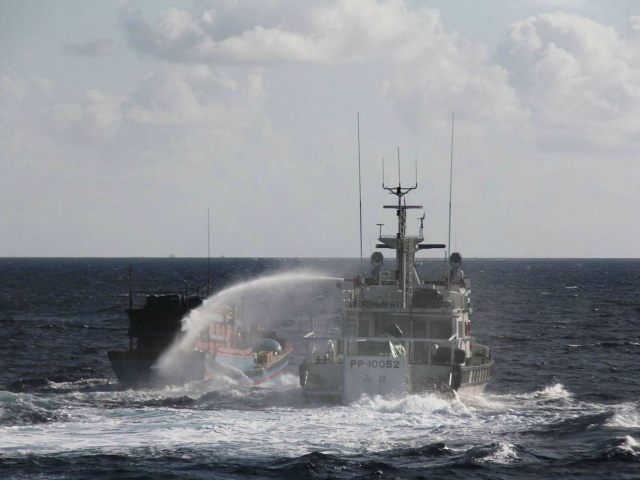 AT SEA : This handout photo taken on January 6, 2016 and released on January 25, 2016 by the Taiwan Coast Guard shows Taiwan's coastguard (R) using a water cannon to spray a Vietnamese fishing boat, some 2.5 nautical miles (around 4,600 metres) off Taiping Island, an Taiwan-administered islet in the disputed Spratlys in the South China Sea. The two Taiwanese coastguard boats, which have been deployed there since December to replace smaller vessels, scrambled to drive off the Vietnamese boats. The Spratly islands are also claimed in part or in whole by Vietnam, China, the Philippines, Malaysia and Brunei. AFP PHOTO / TAIWAN COAST GUARD