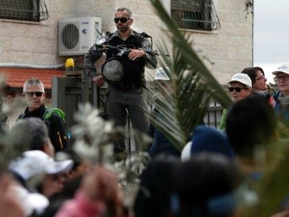 An Israeli policeman stands guarding the street as Christian worshippers attend a procession during the Palm Sunday march at the Mount of Olives in Jerusalem on March 20, 2016.