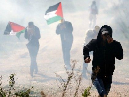 Palestinian protesters, some holding national flags, run away from tear gas smoke during clashes with Israeli security forces following a march on February 19, 2016 in the West Bank village of Bilin, near Ramallah, to mark the 11th anniversary of their uprising against the building of Israel's controversial separation barrier …