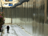 A Muslim man walks by the 'separation barrier' or 'security fence' in East Jerusalem on November 27, 2014 in Jerusalem, Israel. Upon completion, the total length of the controversial wall will be approximately 700 kilometers (430æmi) and include on the western side approximately 9.4% of the West Bank and 23,000 …