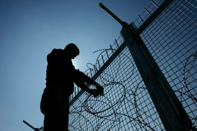 A worker installs barbed wire to a border fence to prevent illegal crossings by migrants at the Bulgarian-Turkish border near Shtit