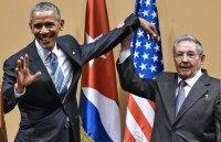 Cuban President Raul Castro (R) raises US President Barack Obama's hand during press conference at the Revolution Palace in Havana on March 21, 2016
