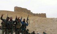 Syrian government forces wave next to the Palmyra citadel