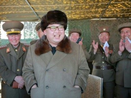 Leader Kim Jong-Un (C) inspects the operation of a new large-caliber multiple rocket launching system at an undisclosed location in North Korea