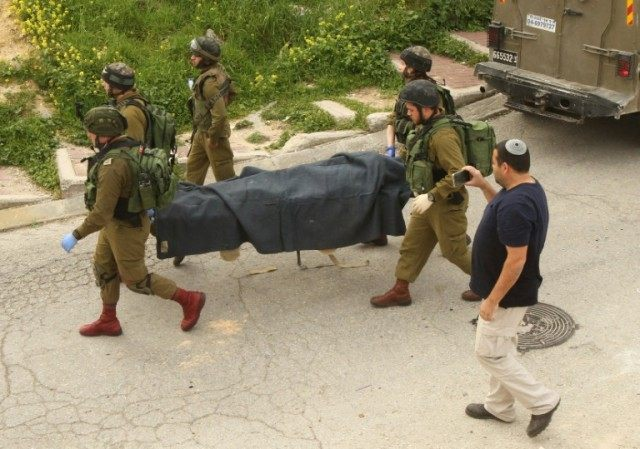 Israeli soldiers remove the body of a Palestinian assailant who was allegedly shot in head by an Israeli soldier, in the West Bank town of Hebron on March 24, 2016