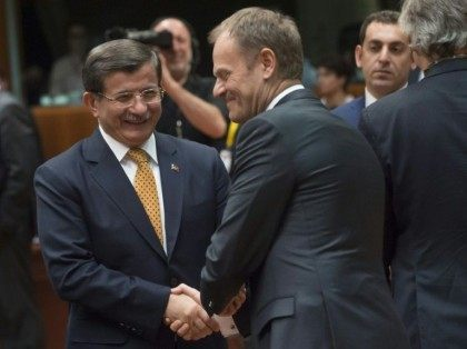 Turkey's Prime Minister Ahmet Davutoglu (L) talks with EU Council President Donald Tusk during the EU summit at headquarters in Brussels on March 18, 2016