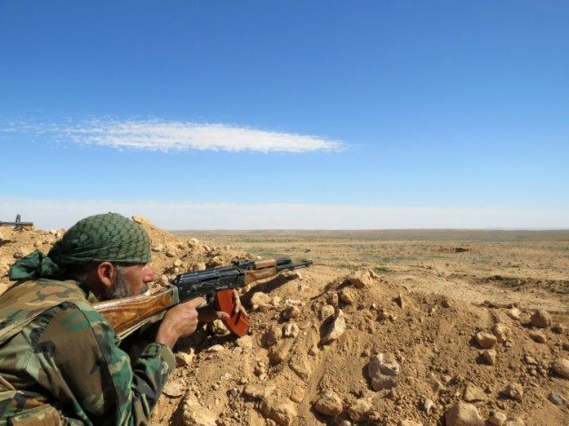 A Syrian army soldier takes aim from a position on the outskirts of Syria's Raqa region on February 19, 2016