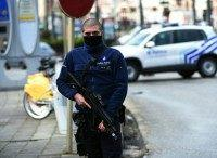 A Belgian police officer stands guard during an anti-terror raid in the Schaerbeek - Schaarbeek district of Brussels, on March 25, 2016
