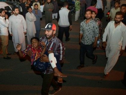 A Pakistani man carries an injured child to the hospital in Lahore on March 27, 2016, after a suicide bomb ripped through the parking lot of a crowded park in the Pakistani city of Lahore