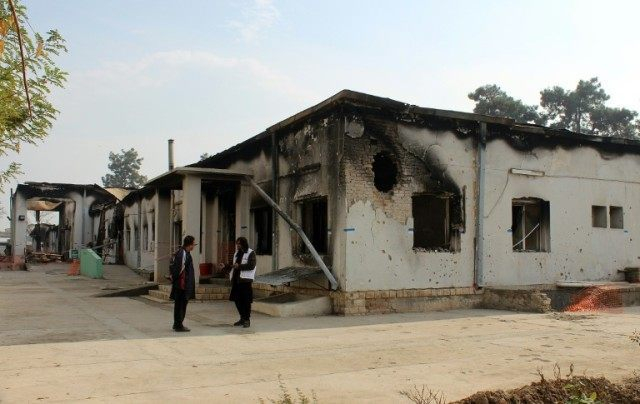 MSF staff stand outside the damaged Medecins Sans Frontieres hospital in northern Kunduz on November 10, 2015, after US forces bombed the hospital, killing at least 30 people, on October 3, 2015