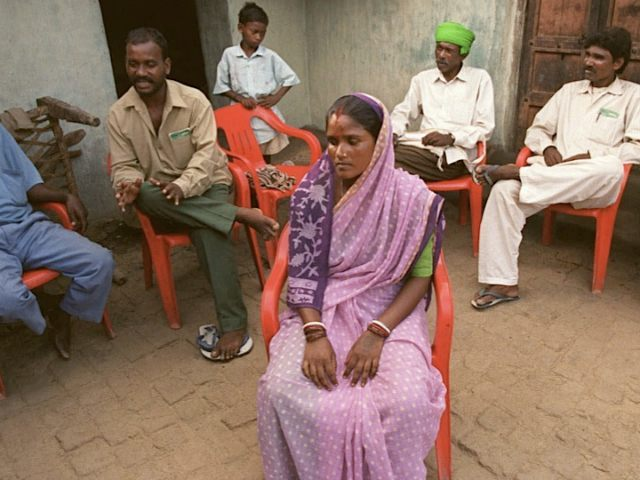 Nomita Puran sits in the courtyard of her home in Dabang village, in the eastern Indian state of Bihar, July 2, 2000, as elders from her community decide on how to defend her after a fellow villager accused her of being a witch. A boy in the village started vomiting …