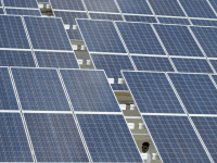 A member of the Presidential Security Group (PSG) walks under the solar panels at the roof deck of a mall in Manila on November 24, 2014. The 5,760 solar panels have been installed on the roof deck of the multi-level carpark of SM City mall.