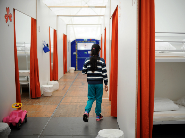 A girl walks in a corridor of a temporary holding centre for asylum seekers in a huge tent in Berlin on March 3, 2015.