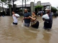 Darius Simon, second from left, helps his mother Carol, evacuate her flooded apartment complex along with his brother Dominique and son, Isaac Hernandez, Monday, April 18, 2016, in Houston. Storms have dumped more than a foot of rain in the Houston area, flooding dozens of neighborhoods and forcing the closure …
