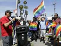 """Students rally outside Santee Education Complex in South Los Angeles on Wednesday, April 20, 2016. The principal of the Los Angeles high school where a scuffle broke out with adult protesters over a new gender-neutral bathroom praised his students Wednesday as """"trailblazers"""" for campaigning to install the restroom. (AP Photo/Nick Ut)"""