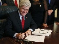Mississippi Gov. Phil Bryant laughs at a joke while he signs HB1, a special session economic package of hundreds of millions of dollars of state money and incentives for a tire plant in western Hinds County and a shipyard in Gulfport, Monday, Feb. 8, 2016 at the Capitol in Jackson, …
