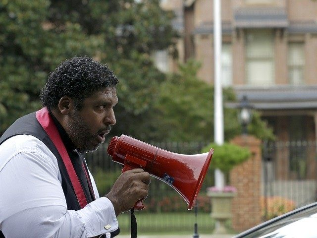 Rev. William Barber, President of the North Carolina branch of the NAACP, speaks to protestors as they march around the executive mansion to demonstrate against voting law changes by the state's Republican-led legislature. (AP Photo/Gerry Broome)