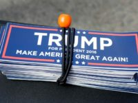 A bundle of stickers in support of Republican presidential candidate Donald Trump rest on a vendor's table before the expected start of a scheduled Trump campaign rally, Monday, April 25, 2016, in Warwick, R.I. (